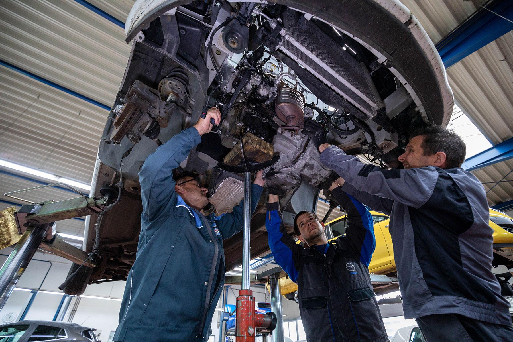 Mechaniker arbeiten unter einem Auto auf der Hebebühne bei Wegst Automobile